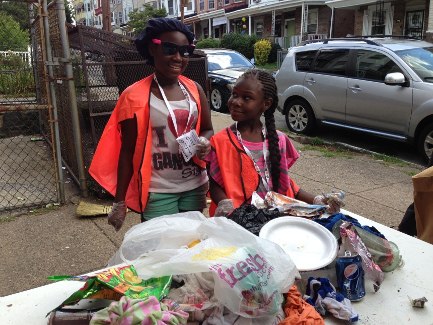 Harmony and Indyia display their trash collection while matching up  their littered items to the scavenger hunt list. Did they find everything?