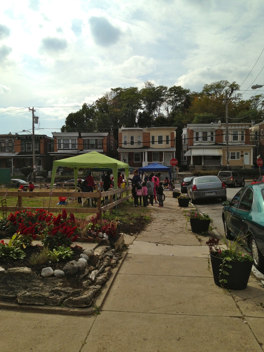 October 2013: After the residents at the last two houses on W Rockland St planted gardens, neighbors worked together to install several flower planters along the border of the lot. It began to look like a space people cared about.