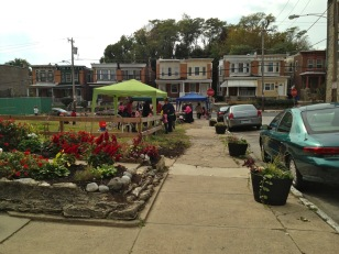 Neighbors held a flea market in the lot in 2013. After the residents at the last two houses planted gardens, neighbors worked together to install several flower planters along the border of the lot.